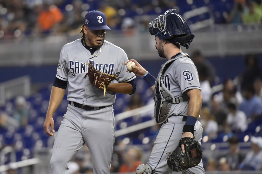 Padres catcher Austin Hedges talks to pitcher Dinelson Lamet during Thursday's game against the Miami Marlins.