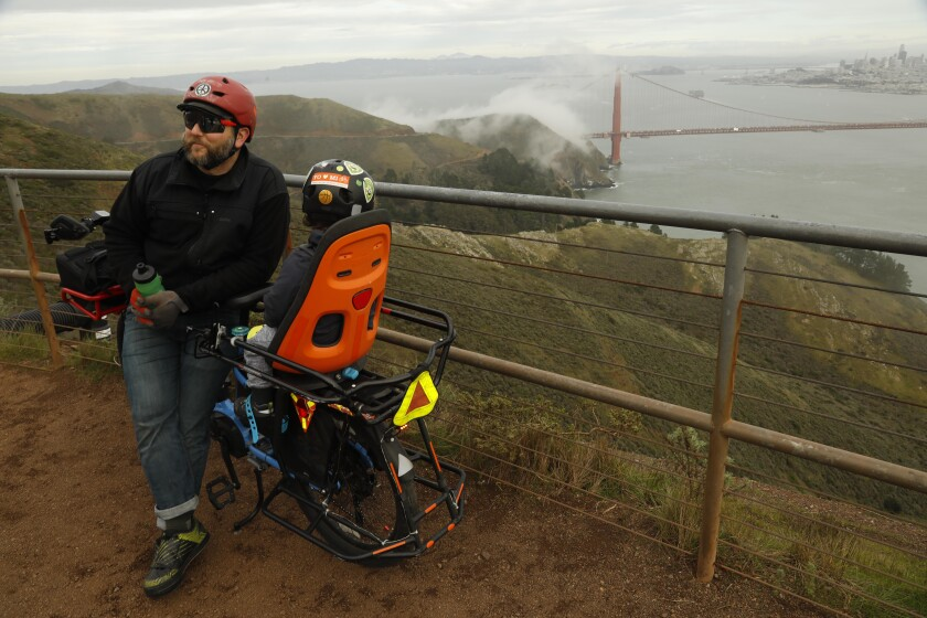 San Francisco resident Matt Dove, 41, and his son Elijah, 3, take a break from riding their e-bike at Hawk Hill overlooking the Golden Gate Bridge in Marin County.