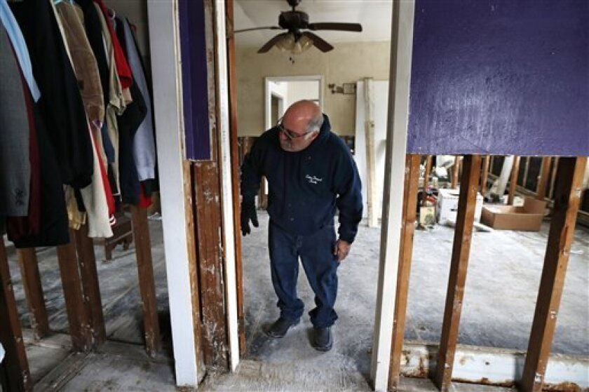 FILE - In this file photo of Jan. 23, 2013, Anthony Cavallo looks at the doorway to the room of his daughter Amy in Union Beach, N.J., where the family has been living in a trailer next to their home damaged by Superstorm Sandy because the house was uninhabitable as they awaited storm aid. Last wee