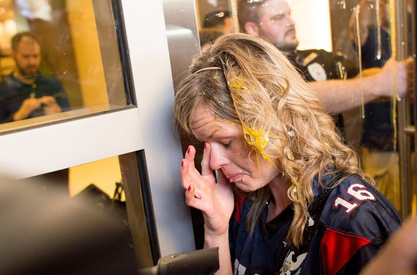 A woman wipes egg off her face after being pursued by protesters while leaving Republican presidential candidate Donald Trump's campaign rally on Thursday, June 2, 2016, in San Jose, Calif. A group of protesters attacked Trump supporters who were leaving the presidential candidate's rally in San Jo
