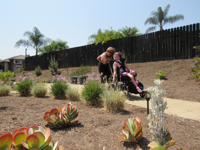 Patricia Wood and her daughter, Kimberly, pause to take in the award-winning garden at their home in Rancho San Diego.