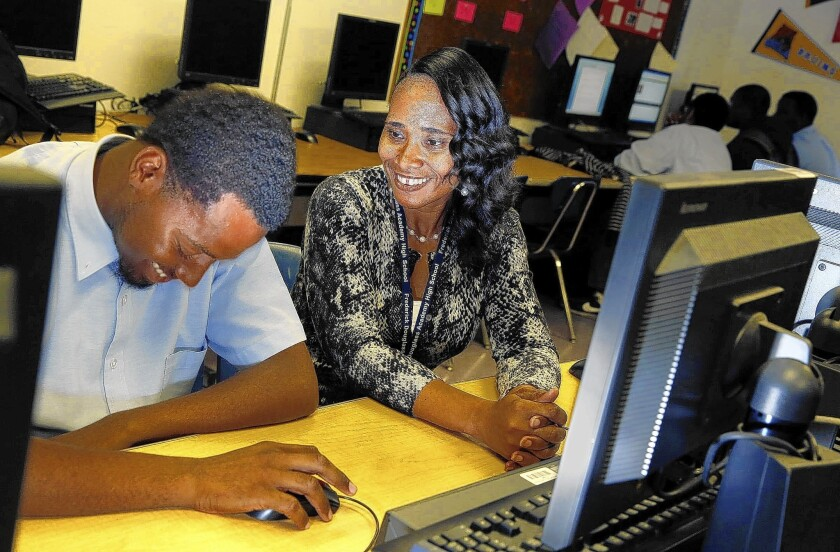 At Fredrick Douglass Academy High School, Principal LaKeyshua Washington banters with senior Charles Rachal, 19, in the computer lab. ICEF had been reluctant to invest in technology upgrades in the former church the group leases for Douglass.