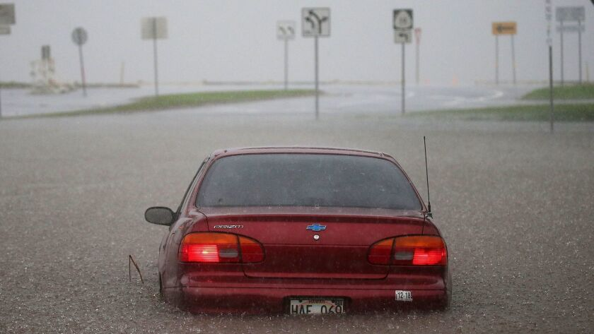 A car is submerged on a street in Hilo, Hawaii. As much as 20 inches of rain fell on the Big Island as Hurricane Lane churned offshore.