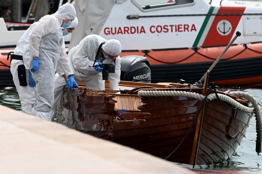 FILE - In this June 21, 2021 file photo, Italian forensic police inspect the damage on a boat as they investigate two German tourists from Munich for a boat collision which killed an Italian man and woman, in Salo', on Lake Garda, northern Italy. Italian authorities say a German man has returned to Italy to surrender himself to police in the criminal probe of a boating accident that killed two Italian boaters last month on Lake Garda. Brescia Prosecutor Francesco Prete told state TV on Monday that besides being investigated for two counts of manslaughter, the suspect is also jailed for failure to help the stricken boaters. (AP Photo/Gabriele Strada, File)