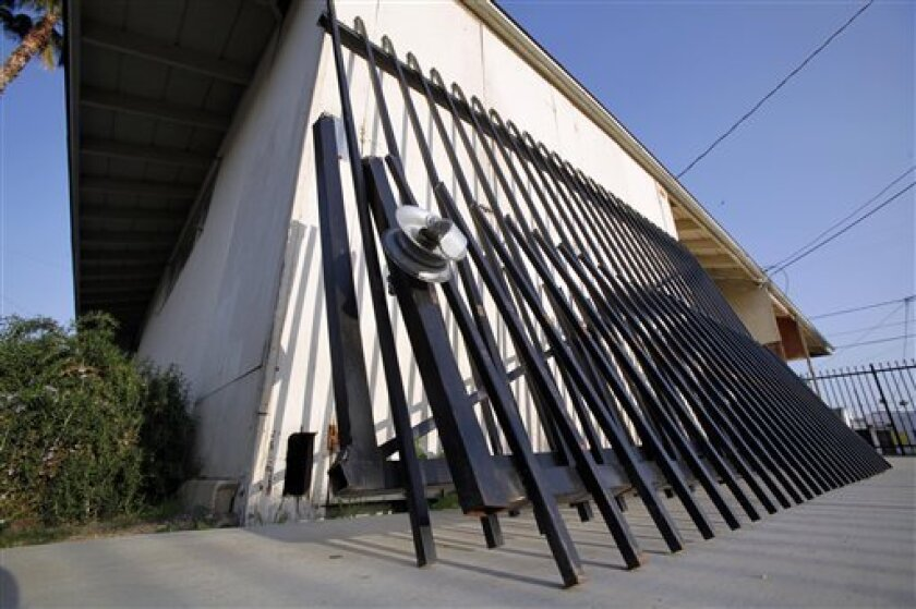A tract home that had been repurposed into the headquarters of the Riverside County Gang Task Force in Hemet, Calif., is seen Thursday, March 18, 2010.  A triggering device attached to a ballistic device narrowly missed wounding a police officer who sought to open the gate, which had been barring a