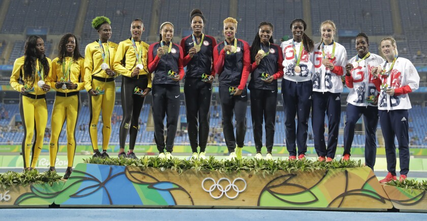 Olympic athletes stand in a line on the medals podium.