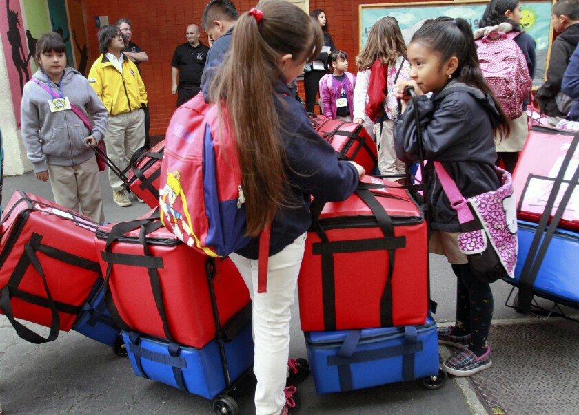 Mayerly Tejano, 7, right, leans on a container that keeps food warm while she chats with her friends at Figueroa Street Elementary School as they prepare to deliver food for a classroom breakfast program.