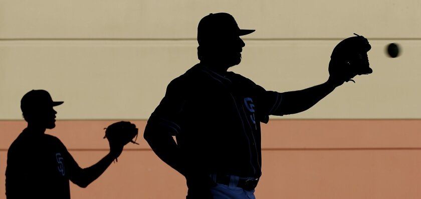Padres pitchers Tayron Guerrero, left, and Leonel Campos catch during spring training baseball practice Saturday, Feb. 20, 2016, in Peoria, Ariz.