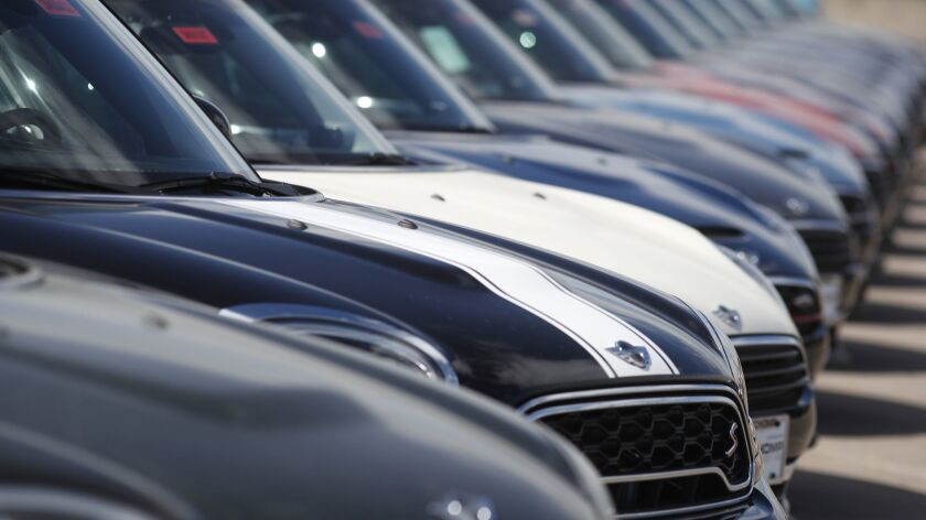 A row of cars for sale at an auto dealership.