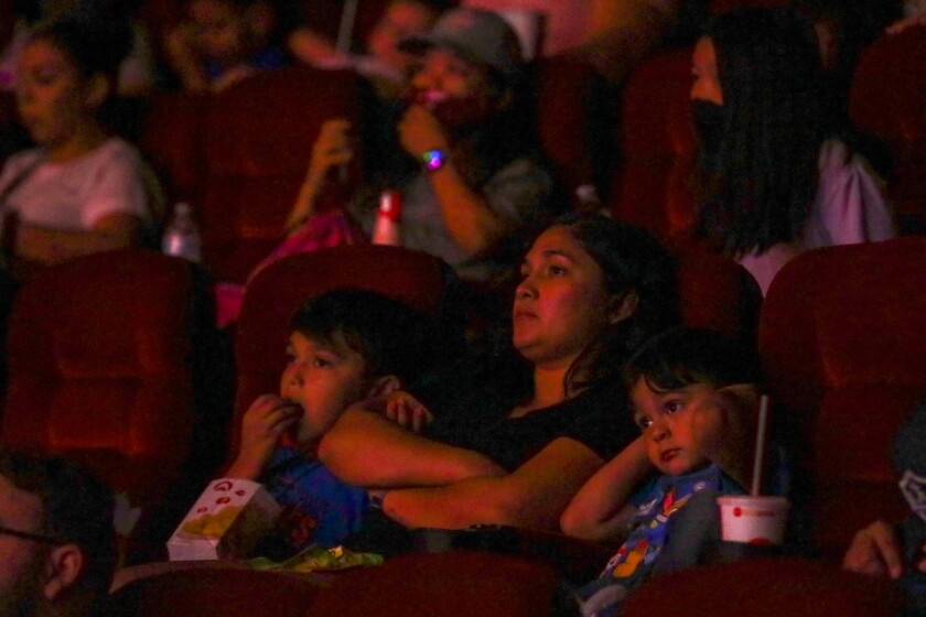 A woman and two kids watch a movie in a theater.
