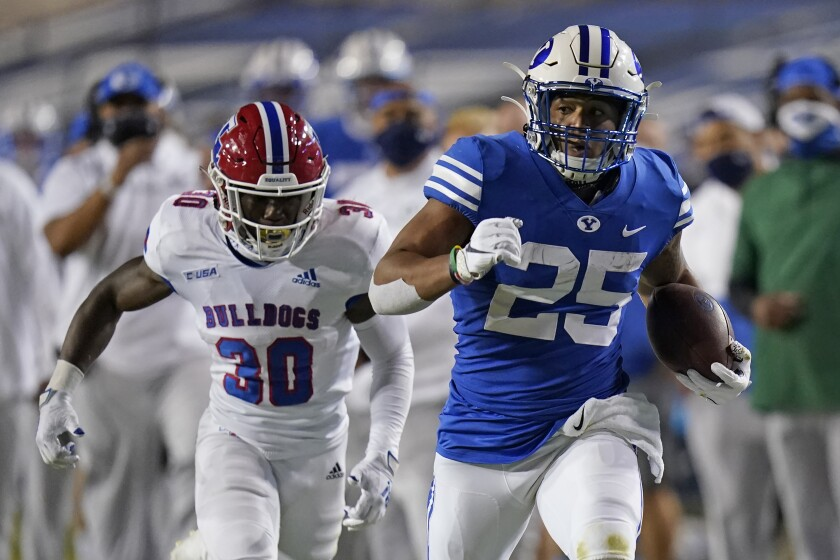 BYU running back Tyler Allgeier (25) carries the ball as Louisiana Tech defensive back Cedric Woods (30) pursues during the second half of an NCAA college football game Friday, Oct. 2, 2020, in Provo, Utah. (AP Photo/Rick Bowmer, Pool)