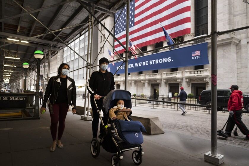A family wearing masks passes the New York Stock Exchange on May 26.