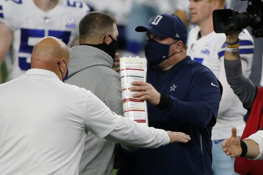 New York Giants head coach Joe Judge, center left, and Dallas Cowboys head coach Mike McCarthy, center right, greet each other after their NFL football game in Arlington, Texas, Sunday, Oct. 11, 2020. (AP Photo/Michael Ainsworth)