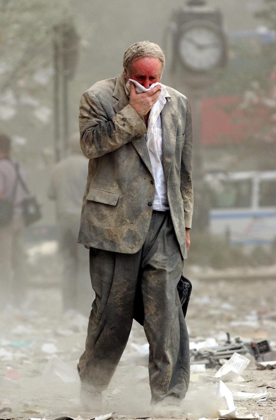 مردی هنگام عبور از میان گرد و خاک و آوار دهان خود را می پوشاند