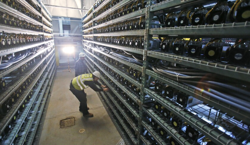 Workers look over racks of bitcoin data miners during construction of a data center in Virginia Beach, Va.