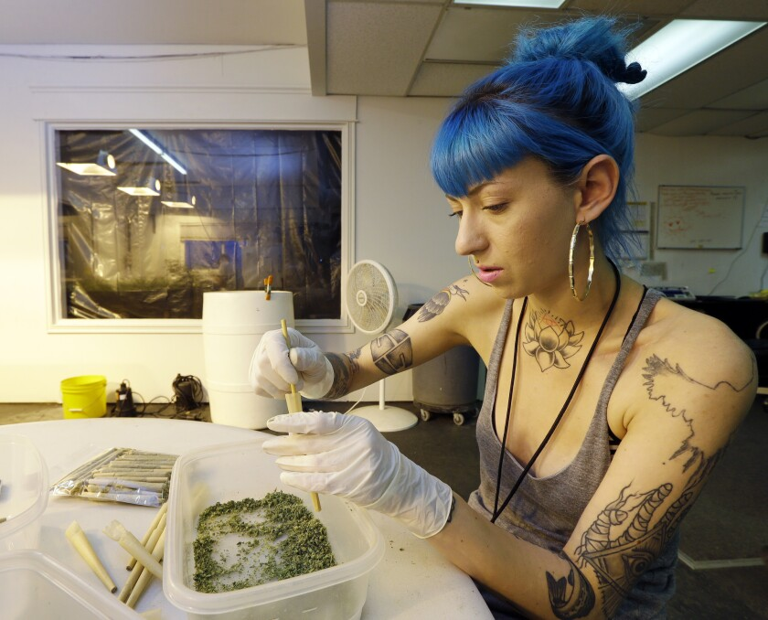 Stevie Askew, a worker at Sea of Green Farms, packs recreational marijuana into blunts that will be sold in stores when legal recreational pot sales begin Tuesday in Washington state.