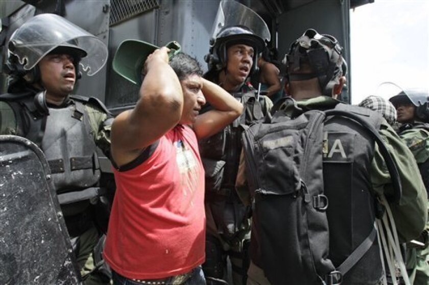 Riot police detain a member of the Ngobe-Bugle ethnic group man after clash with riot police at the Pan American highway in San Felix, Panama, Sunday, Feb. 5, 2012. A group of indigenous protesters has blockaded the Pan-American Highway in Panama for days to protest the recent approval of mines and reservoirs in their region. (AP Photo/Arnulfo Franco)