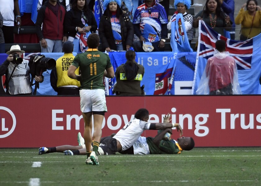 South Africa's Sakoyisa Makata scores against Fiji's Kavekini Tabu in the Rugby Sevens tournament final Sunday at Dignity Health Sports Park.