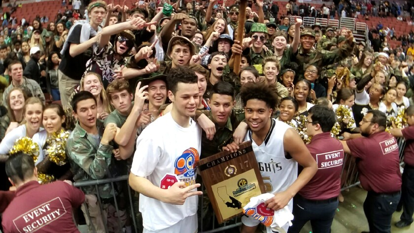 Bishop Montgomery's Jordan Schakel, left, and Ethan Thompson celebrate with fans while holding the Southern Section Open Division championship plaque at the Honda Center on Saturday night.