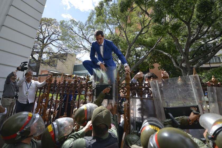 Venezuelan National Assembly President Juan Guaido tries to climb the fence to enter the legislative compound after he and other opposition lawmakers were blocked by police from attending a special session in Caracas on Jan. 5, 2020.