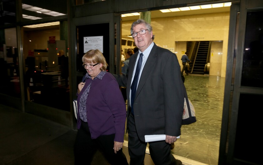 Former Times columnist T.J. Simers and his wife, Ginny, leaving court in 2015.