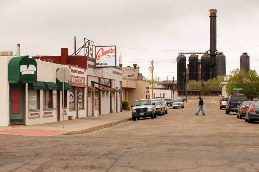 A person crossing a street lined with shops, passing in front of a steel mill at the end of the street.