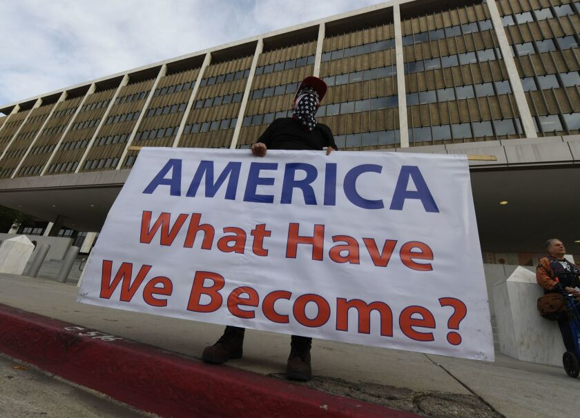 "An immigrant rights activist holds a sign reading ""America what have we become?"" outside L.A. federal building in 2018"