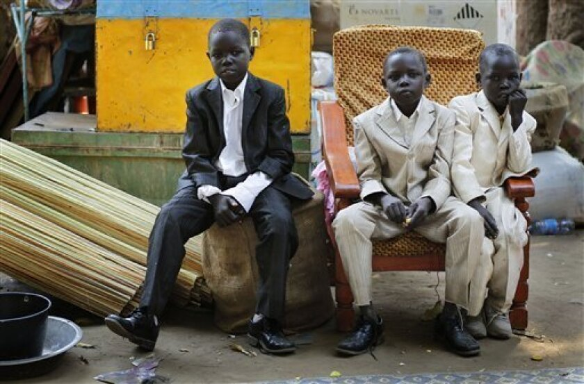 South Sudanese children dressed in their Sunday best, who returned to the South by barges on the Nile river, sit amidst their belongings in Juba's port, Tuesday, Jan. 11, 2011. About four million Southern Sudanese voters began casting their ballots Sunday in a weeklong referendum on independence that is expected to split Africa's largest nation in two. (AP Photo/Jerome Delay)