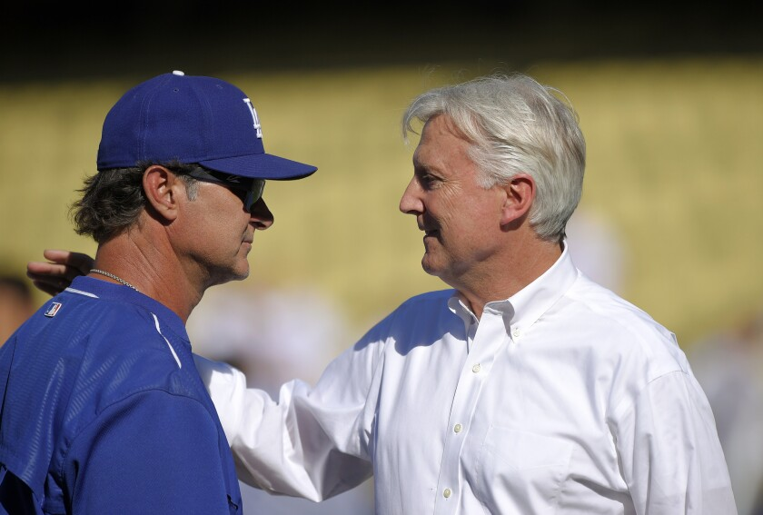 Dodgers Manager Don Mattingly talks with team co-owner Mark Walter, right, before a game against the Cincinnati Reds on Aug. 14.