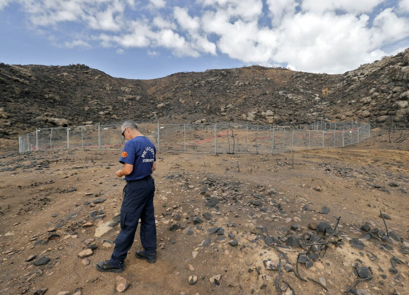 Prescott, Ariz., firefighter Wade Ward stands alone in July at the fenced-in site where 19 firefighters died battling an wildfire on June 30.