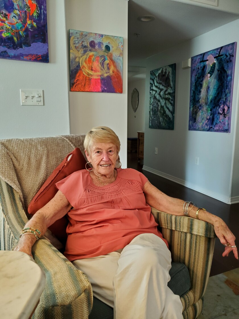 La Jolla resident and ovarian cancer survivor Annette McElhiney is surrounded by paintings she created.