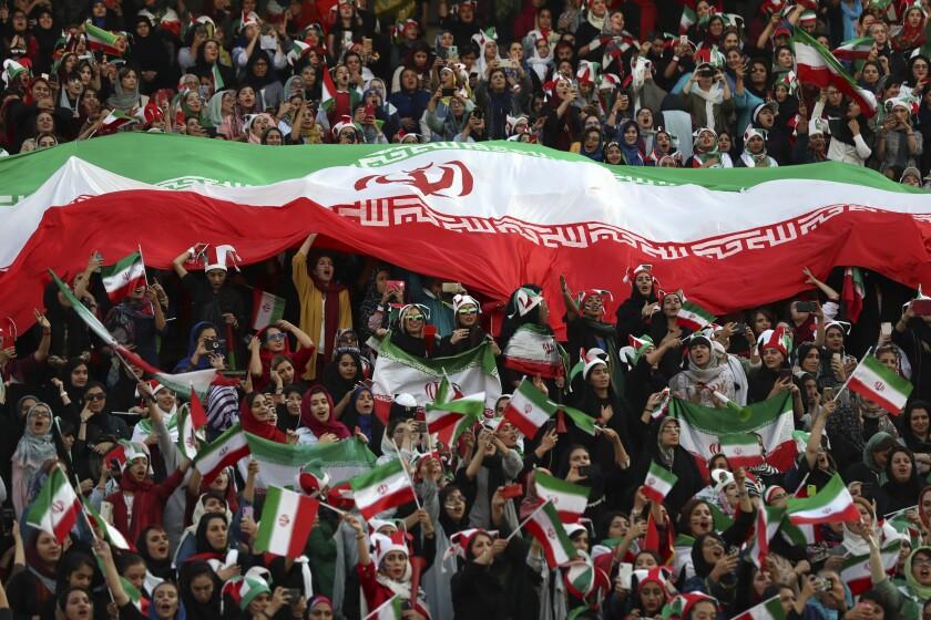 Iranian women holding an Iranian flag cheer