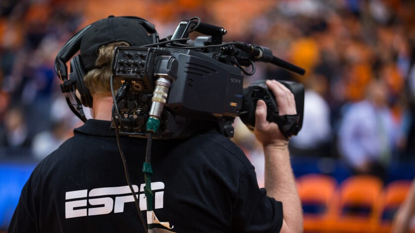 A cameraman working for ESPN network operates a camera at court side.