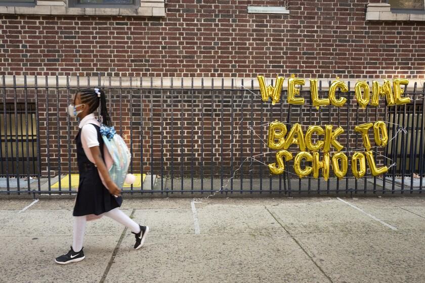 """un cartel de """"Bienvenidos de vuelta a la escuela"""" en el primer día de clases"""