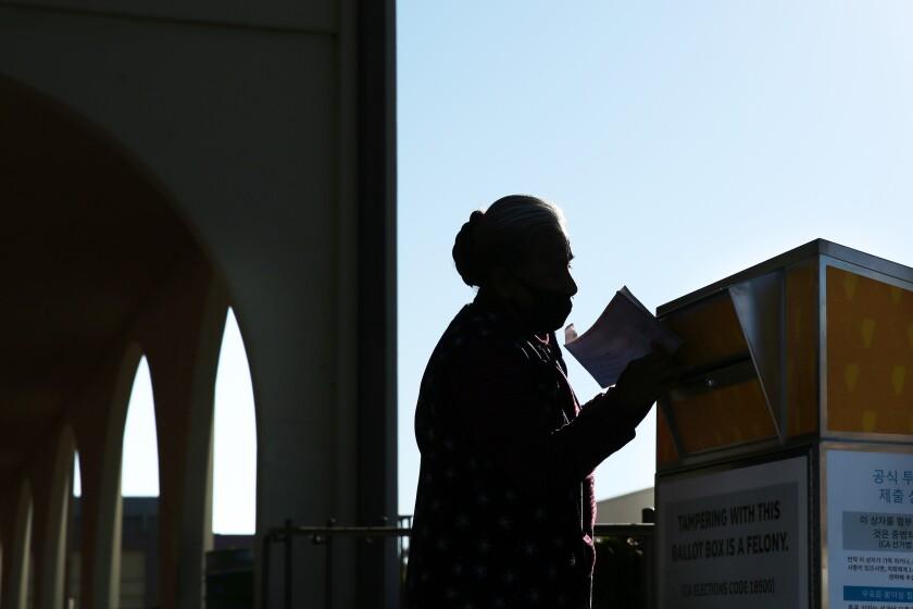 A voter drops a ballot into a box.