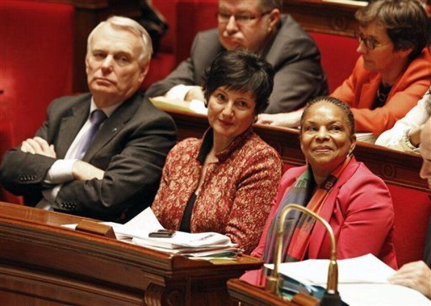 French justice minister Christiane Taubira, right, sits on the government bench with social affairs minister Dominique Bertinotti, center, and prime minister Jean Marc Ayrault, during the vote at the National Assembly in Paris, Tuesday Feb. 12, 2013, of a new law legalizing gay marriage.  France's