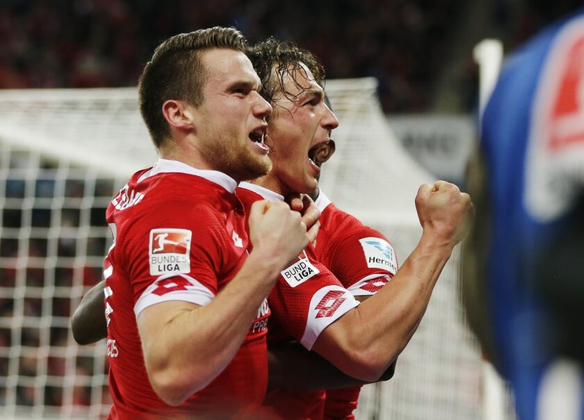 Mainz's Julian Baumgartlinger, right, celebrates his side's second goal during a German Bundesliga soccer match between FSV Mainz 05 and FC Schalke 04 in Mainz, Germany, Friday, Feb. 12, 2016. (AP Photo/Michael Probst)