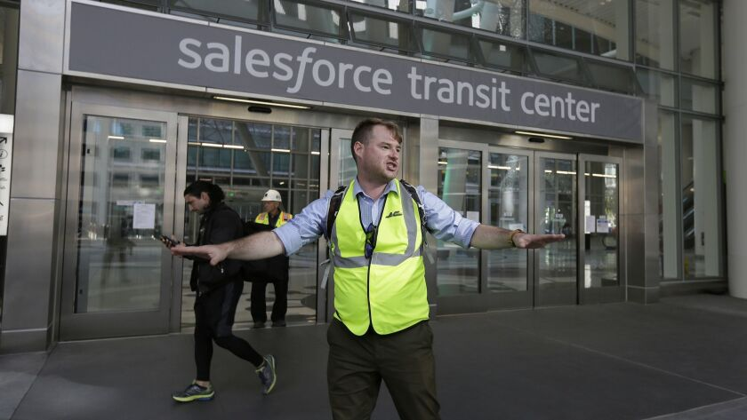 Mike Eshleman, with AC Transit, directs people away from the Salesforce Transit Center following its