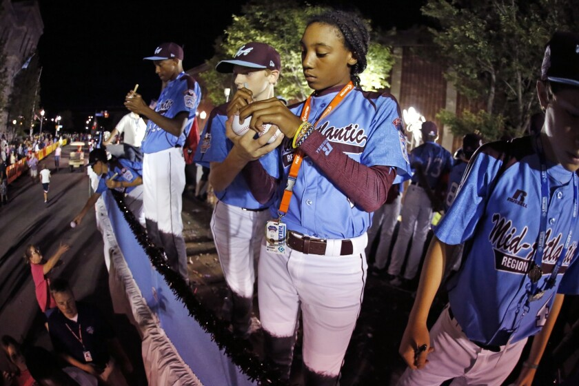 Philadelphia pitcher Mo'ne Davis signs baseballs while riding in the Little League Grand Slam Parade as it makes its way through downtown Williamsport, Pa. on Aug. 13.
