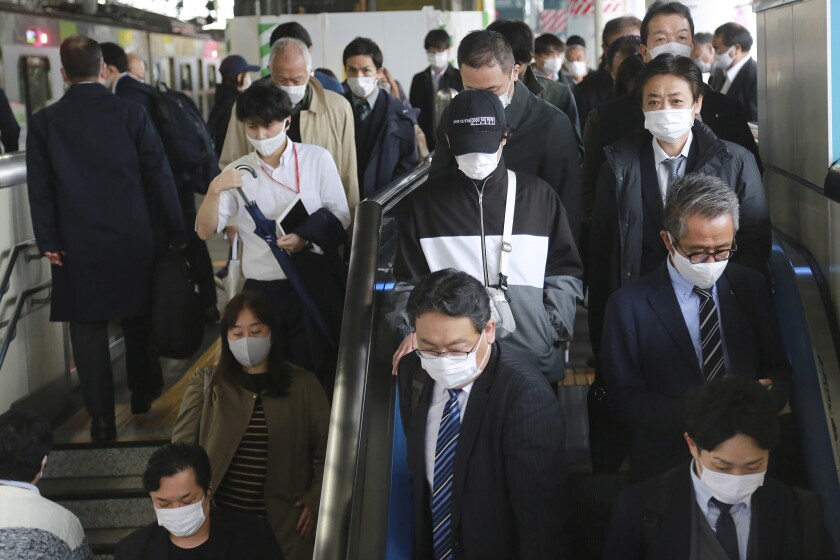 People wearing face masks to protect against the spread of the coronavirus arrive at the train station in Tokyo, Wednesday, Nov. 25, 2020. (AP Photo/Koji Sasahara)