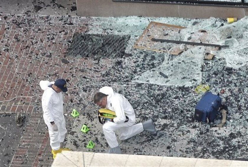 Two men in hazardous materials suits put numbers on the shattered glass and debris as they investigate the scene at the first bombing on Boylston Street in Boston Tuesday, April 16, 2013 near the finish line of the 2013 Boston Marathon, a day after two blasts killed three and injured over 170 people. The bombs that ripped through the Boston Marathon crowd were fashioned out of ordinary kitchen pressure cookers, packed with nails and other fiendishly lethal shrapnel, and hidden in duffel bags lef