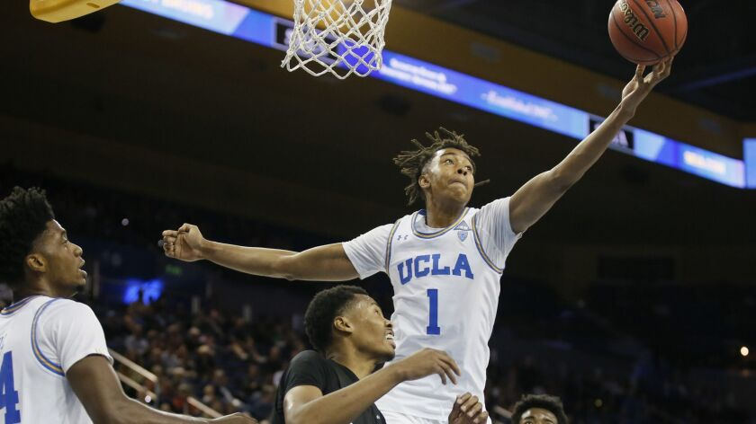 UCLA center Moses Brown reaches for a rebound over Long Beach State forward KJ Byers, left, and forw
