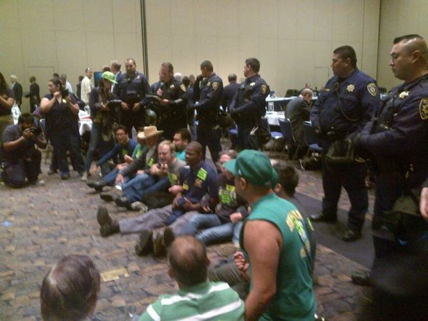 Technical health workers at the five UC medical centers are threatening a two-day strike next week, and a group of them disrupted the start of the regents' meeting Wednesday with a sit-down protest that led to 13 arrests.