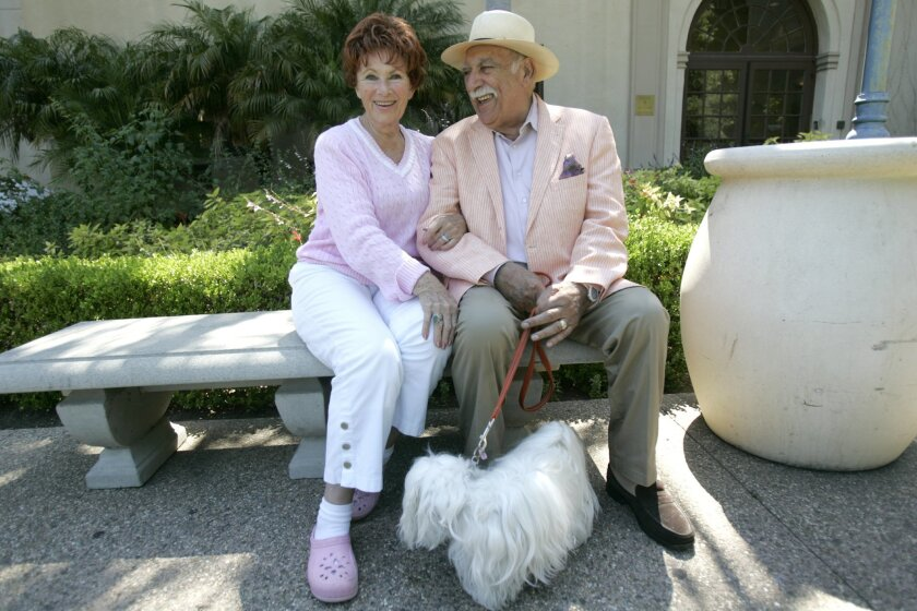 Marion Ross and Paul Michael sit on a bench in Balboa Park's Alcazar Gardens with Blanche, the couple's petite Coton de Tulear.