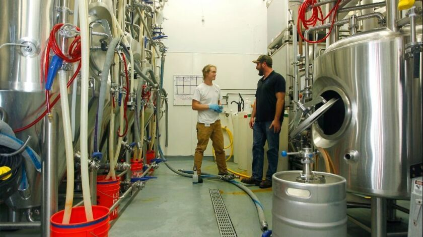 Tyler Carter, left, cleans lines to fermenters as he talks with head brewer Joe Kurowski at White Labs in Mira Mesa.