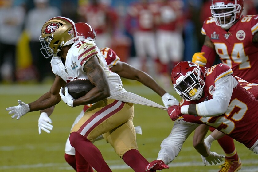 FILE - In this Feb. 2, 2020, file photo, Kansas City Chiefs defensive end Frank Clark, right, tries to tackle San Francisco 49ers running back Raheem Mostert during the first half of the NFL Super Bowl 54 football game in Miami Gardens, Fla. The 49ers open their season against the Arizona Cardinals this week. (AP Photo/David J. Phillip, File)