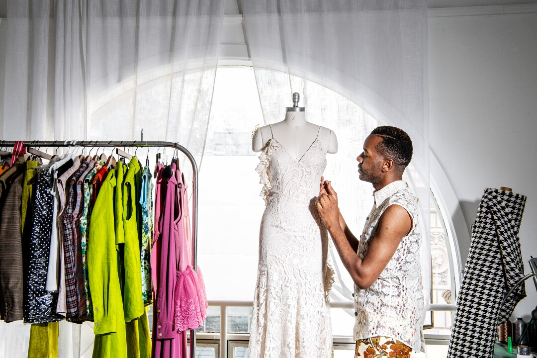 Portrait of fashion designer Kenneth Nicholson wearing a sleeveless lace tailored shirt with contrasting velvet buttons.