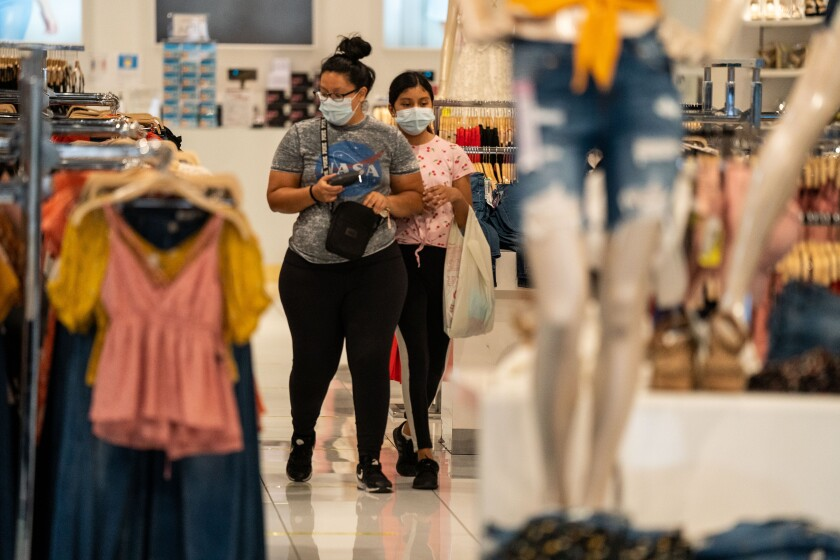 Masked shoppers browse inside Papaya while wandering the Glendale Galleria on Thursday.