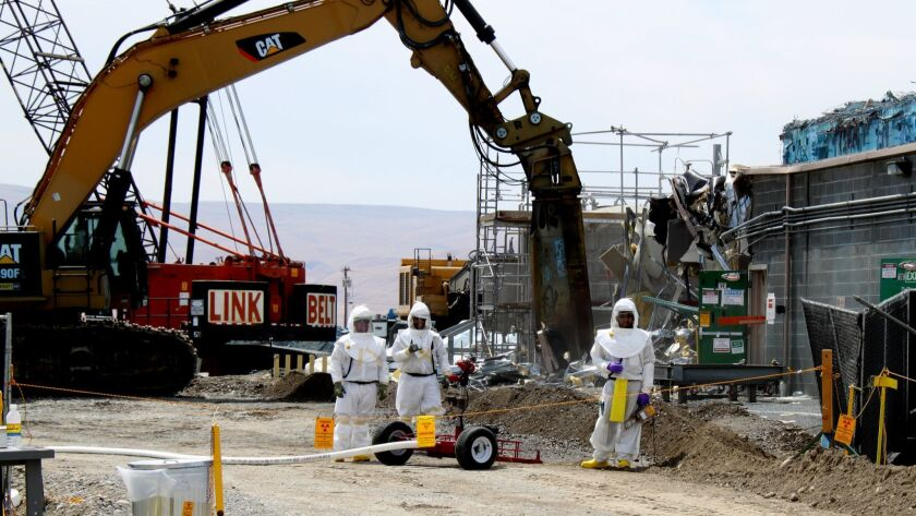 The Energy Department project to tear down the Plutonium Finish Plant at the Hanford Site was halted in mid-December after radioactive dust was discovered far off the plant site. The hazardous work requires workers in protective gear.