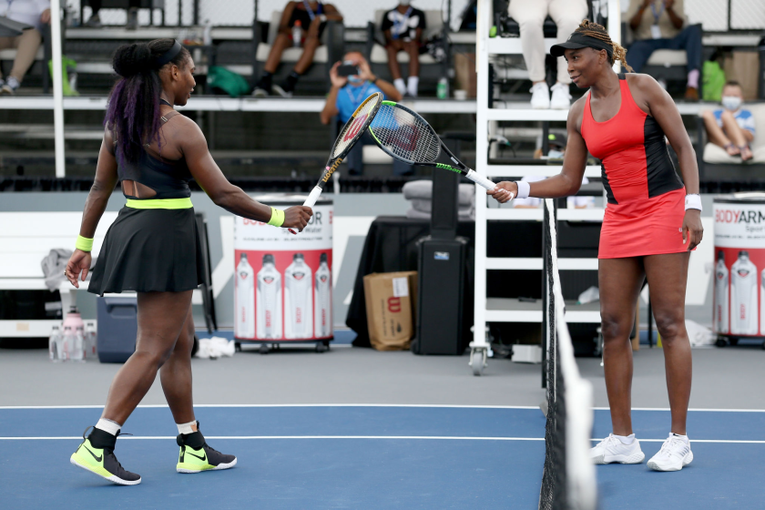 Serena, left, and Venus Williams touch rackets after their Top Seed match.